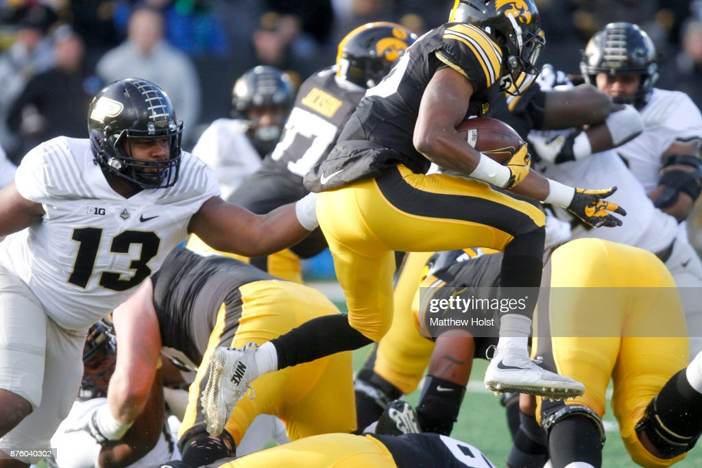 Running back Akrum Wadley #25 of the Iowa Hawkeyes rushes during the first quarter past defensive end Gelen Robinson #13 of the Purdue Boilermakers on November 18, 2017 at Kinnick Stadium in Iowa City, Iowa.