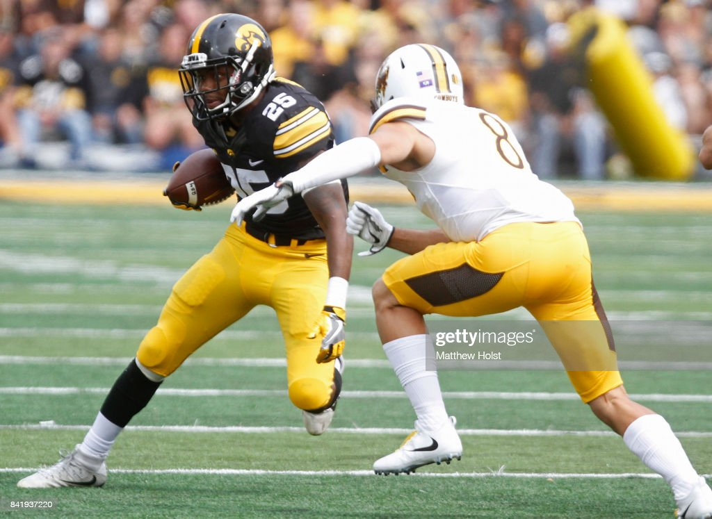 Running back Akrum Wadley #25 of the Iowa Hawkeyes rushes up field during the first quarter in front of linebacker Jalen Ortiz #8 of the Wyoming Cowboys, on September 2, 2017 at Kinnick Stadium in Iowa City, Iowa.