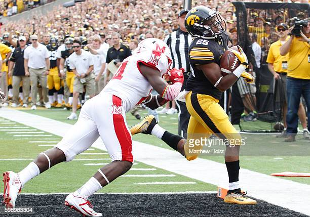 Running back Akrum Wadley of the Iowa Hawkeyes scores a touchdown during the first quarter in front of defensive back Tony Reid of the Miami RedHawks...