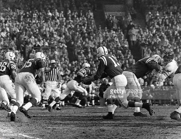 Running back Alan Ameche of the Baltimore Colts looks for the hand off from Hall of Fame quarterback Johnny Unitas in a 3116 win over the New York...