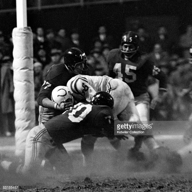Running back Alan Ameche of the Baltimore Colts tries to break through the New York Giants defenders Dick Modzelewski Emlen Tunnell and Sam Huff...