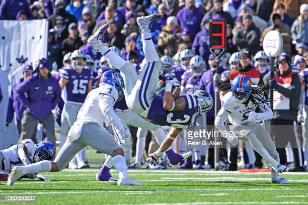 Running back Alex Barnes of the Kansas State Wildcats leaps for extra yardage between cornerback Shakial Taylor and safety Bryce Torneden of the...
