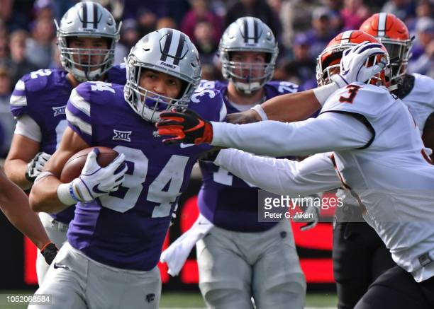 Running back Alex Barnes of the Kansas State Wildcats runs up field against pressure from linebacker Kenneth EdisonMcGruder of the Oklahoma State...