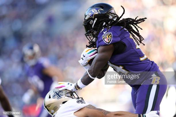 Running Back Alex Collins of the Baltimore Ravens carries the ball in the first quarter against the New Orleans Saints at MT Bank Stadium on October...