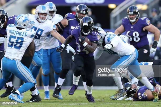 Running Back Alex Collins of the Baltimore Ravens carries the ball in the third quarter against the Detroit Lions at MT Bank Stadium on December 3...