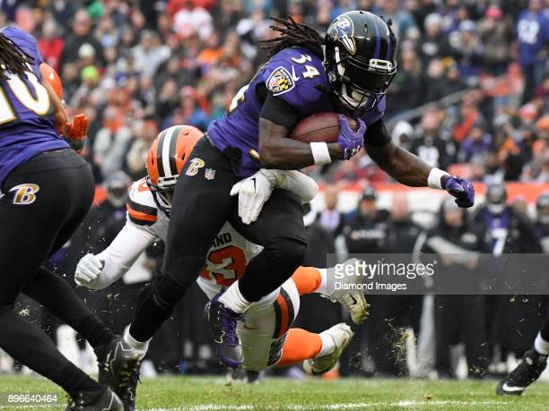 Running back Alex Collins of the Baltimore Ravens carries the ball downfield as he is tackled by linebacker Joe Schobert of the Cleveland Browns in...
