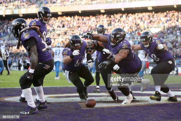 Running Back Alex Collins of the Baltimore Ravens celebrates with teammates after a touchdown in the fourth quarter against the Detroit Lions at MT...