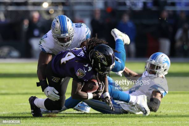 Running Back Alex Collins of the Baltimore Ravens is tackled by linebacker Jarrad Davis of the Detroit Lions in the second quarter at MT Bank Stadium...
