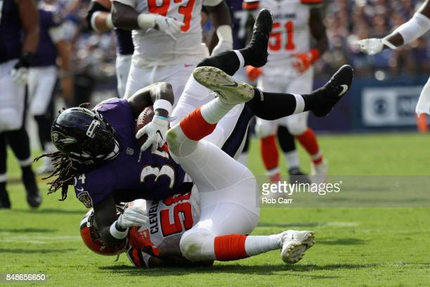 Running back Alex Collins of the Baltimore Ravens is tackled by outside linebacker Christian Kirksey of the Cleveland Browns at MT Bank Stadium on...