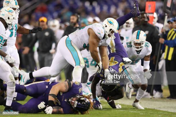 Running Back Alex Collins of the Baltimore Ravens is tackled by defensive tackle Ndamukong Suh of the Miami Dolphins in the fourth quarter at MT Bank...