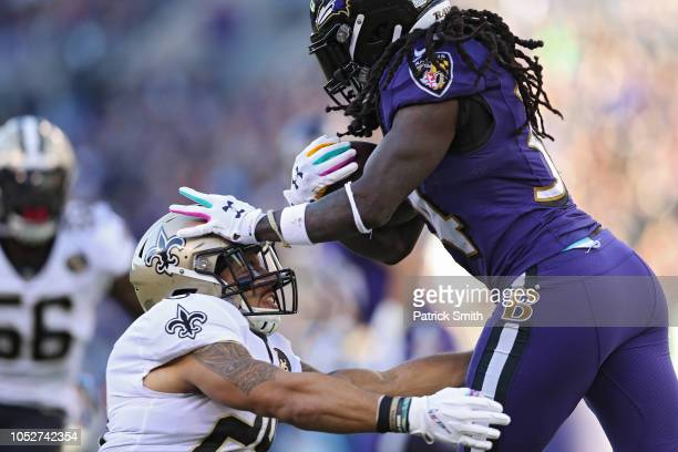 Running Back Alex Collins of the Baltimore Ravens stiff arms Kurt Coleman of the New Orleans Saints as he carries ball in the first quarter against...