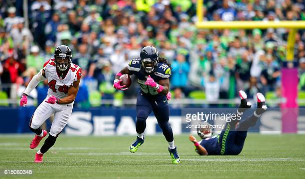 Running back Alex Collins of the Seattle Seahawks takes a pass upfield against the Atlanta Falcons at CenturyLink Field on October 16 2016 in Seattle...