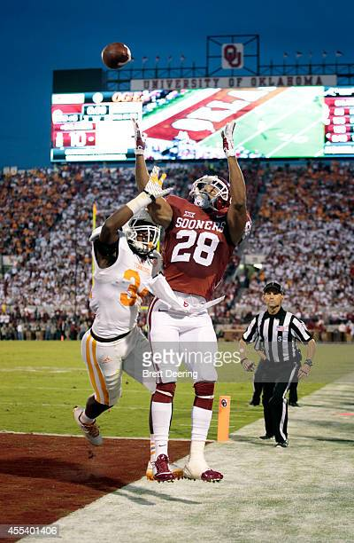 Running back Alex Ross of the Oklahoma Sooners tries to catch a touchdown pass as linebacker Jalen Reeves-Maybin of the Tennessee Volunteers defendes...