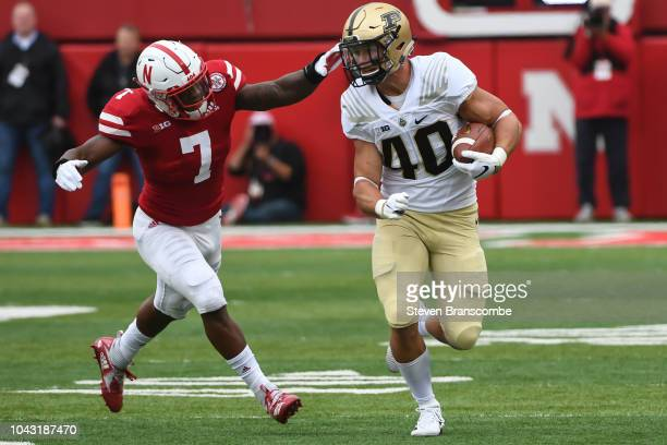 Running back Alexander Horvath of the Purdue Boilermakers runs from linebacker Mohamed Barry of the Nebraska Cornhuskers in the first half at...