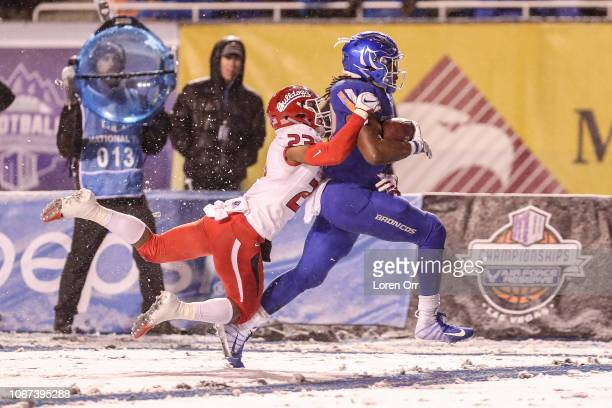 Running back Alexander Mattison of the Boise State Broncos drags defensive back Juju Hughes of the Fresno State Bulldogs enroute to a touchdown...