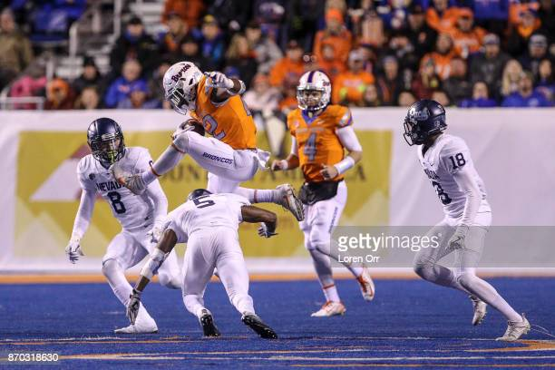 Running back Alexander Mattison of the Boise State Broncos jumps right over the tackle attempt of defensive back Dameon Baber of the Nevada Wolfpack...