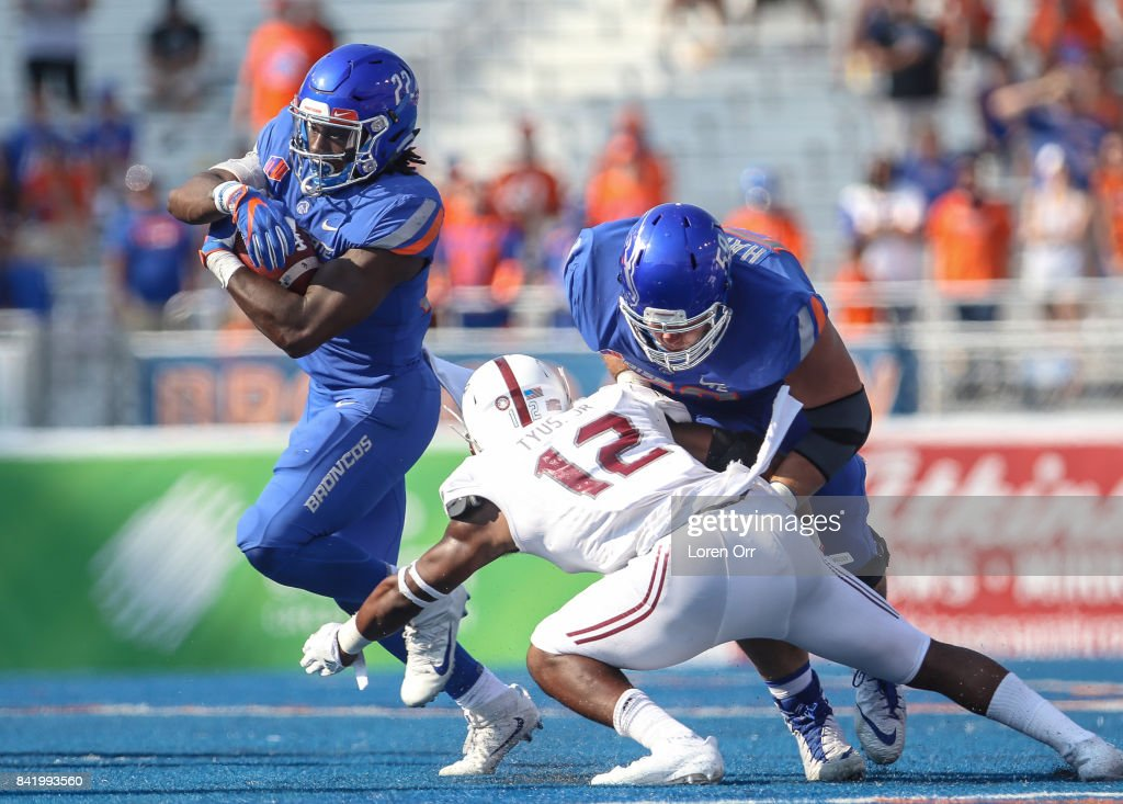 Running back Alexander Mattison #22 of the Boise State Broncos runs through the tackle of safety Melvin Tyus #12 of the Troy Trojans during second half action on September 2, 2017 at Albertsons Stadium in Boise, Idaho. Boise State won the game 24-13.