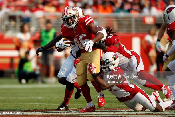 Running back Alfred Morris of the San Francisco 49ers is tackled by cornerback Patrick Peterson of the Arizona Cardinals and linebacker Josh Bynes...