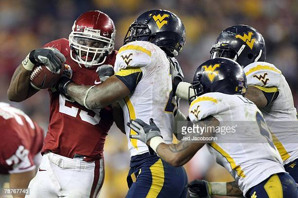 Running back Allen Patrick of the Oklahoma Sooners is brought down by three West Virginia Mountaineers defenders at the Tostito's Fiesta Bowl at...