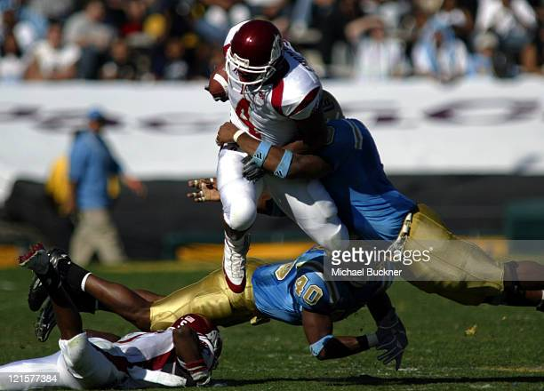 Running back Allen Thompson of Washington State University is wrapped up by linebacker Justin London of UCLA during the 3129 defeat over UCLA at the...