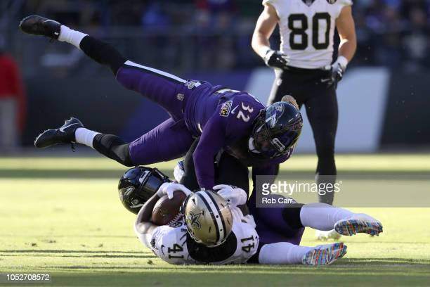 Running Back Alvin Kamara of the New Orleans Saints is tackled by linebacker CJ Mosley and free safety Eric Weddle of the Baltimore Ravens in the...