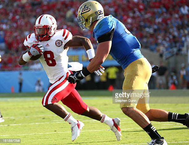 Running back Ameer Abdullah of the Nebraska Cornhuskers carries on a six yard touchdown run in the first quarter against linebacker Jordan Zumwalt of...
