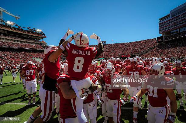 Running back Ameer Abdullah of the Nebraska Cornhuskers jumps on a huddle of teammates before their game against the Idaho State Bengals during their...
