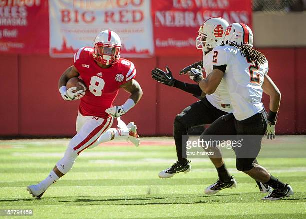 Running back Ameer Abdullah of the Nebraska Cornhuskers runs around the Idaho State Bengals defense during their game at Memorial Stadium on...