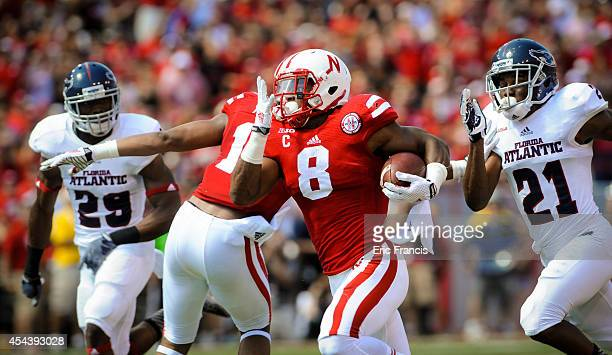 Running back Ameer Abdullah of the Nebraska Cornhuskers runs for a first down past defensive back D'Joun Smith and defensive back Sharrod Neasman of...