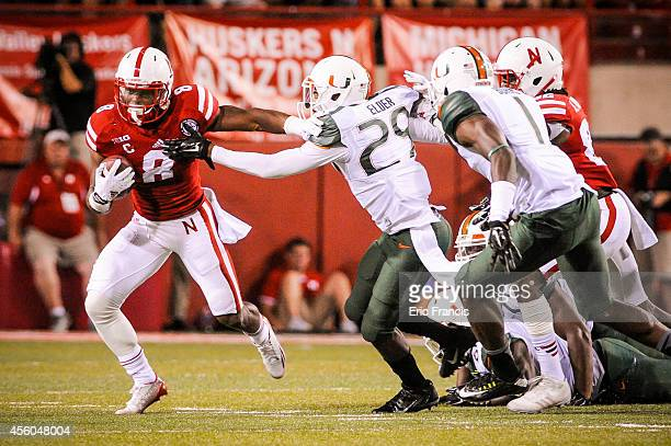 Running back Ameer Abdullah of the Nebraska Cornhuskers slips past defensive back Corn Elder of the Miami Hurricanes during their game at Memorial...