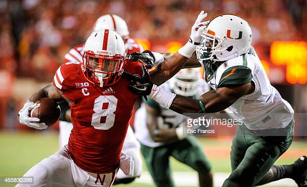 Running back Ameer Abdullah of the Nebraska Cornhuskers stiff arms defensive back Artie Burns of the Miami Hurricanes during their game at Memorial...