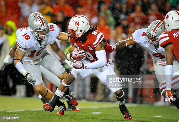 Running back Ameer Abdullah of the Nebraska Cornhuskers tries to slip between defensive back Zach Domicone of the Ohio State Buckeyes and defensive...