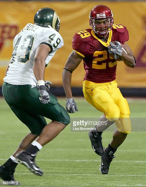 Running back Amir Pinnix of the Minnesota Golden Gophers tries to get past linebacker John Nichols of the Colorado State Rams on September 10 2005 at...