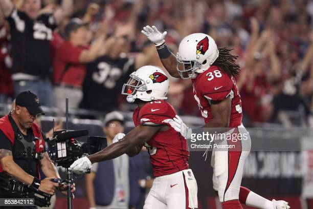 Running back Andre Ellington of the Arizona Cardinals celebrates with wide receiver Jaron Brown after a first quarter touchdown during the NFL game...