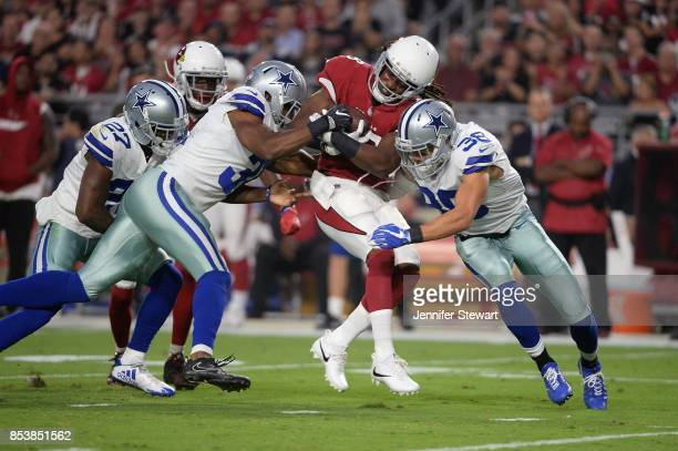 Running back Andre Ellington of the Arizona Cardinals is hit by strong safety Jeff Heath of the Dallas Cowboys and free safety Byron Jones of the...