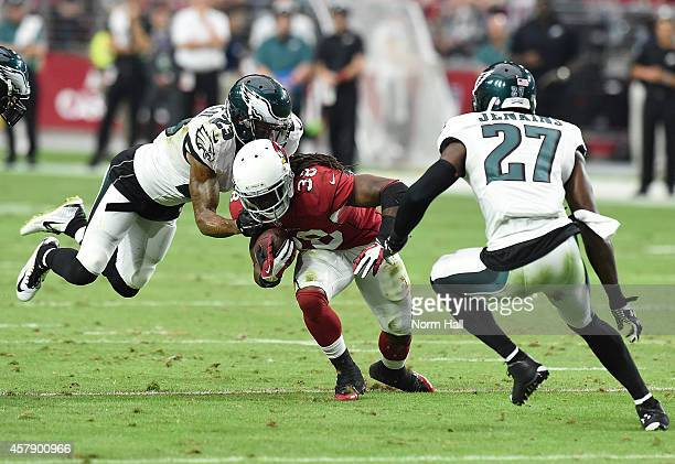Running back Andre Ellington of the Arizona Cardinals runs the ball against cornerback Nolan Carroll and free safety Malcolm Jenkins of the...