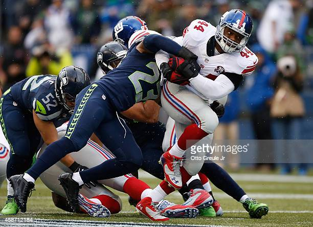 Running back Andre Williams is tackled by strong safety Jeron Johnson of the Seattle Seahawks during the second quarter of the game at CenturyLink...