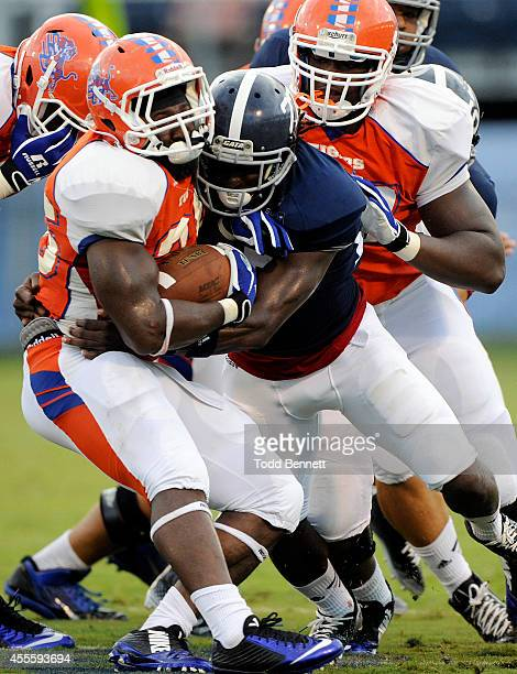 Running back Anthony Criswell Jr #36 of the Savannah State Tigers is tackled by linebacker Deshawntee Gallon of the Georgia Southern Eagles during...