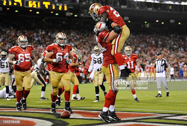 Running back Anthony Dixon of the San Francisco 49ers jumps into the arms of tackle Joe Staley after scoring a touchdown against the New Orleans...
