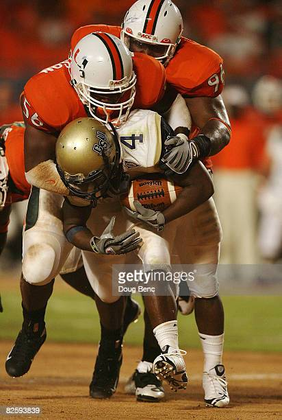 Running back Antwan Ivey of the Charleston Southern Buccaneers is brought down by Marcus Robinson and Antonio Dixon of the Miami Hurricanes at...