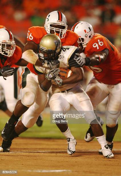 Running back Antwan Ivey of the Charleston Southern Buccaneers is brought down by defensive lineman Marcus Robinson of the Miami Hurricanes at...