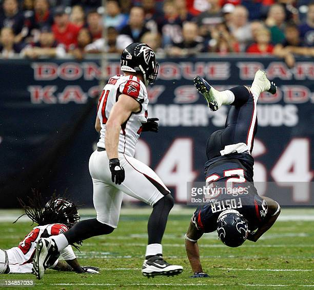 Running back Arian Foster of the Houston Texans is upended by cornerback Dunta Robinson of the Atlanta Falcons at the end of the second quarter at...