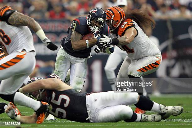 Running back Arian Foster of the Houston Texans runs the ball against Domata Peko of the Cincinnati Bengals during their 2012 AFC Wild Card Playoff...