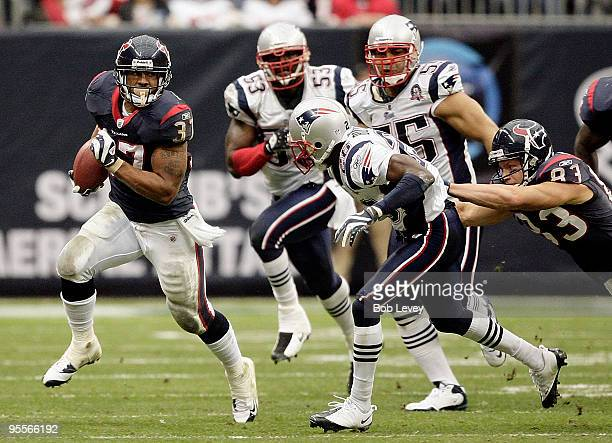 Running back Arian Foster of the Houston Texans rushes along the sideline as safety Brandon Meriweather of the New England Patriots looks to make the...