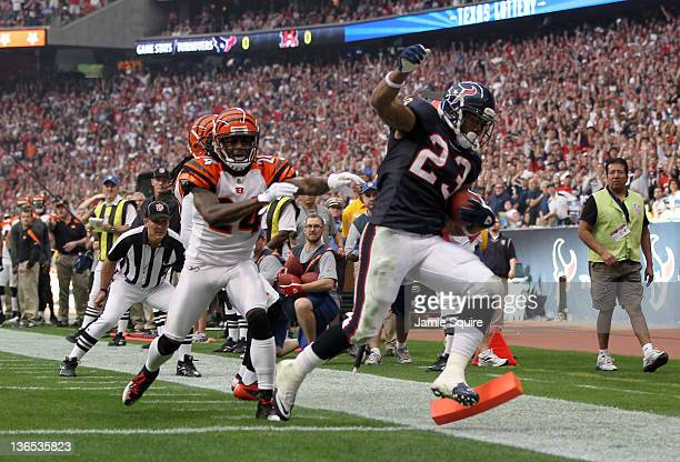 Running back Arian Foster of the Houston Texans scores on an eight-yard touchdown run in the first quarter in front of cornerback Adam Jones of the...