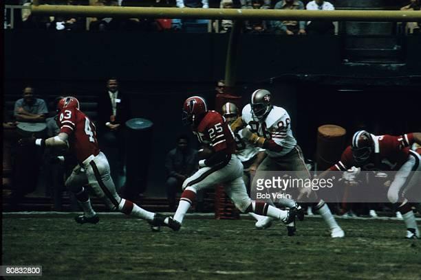 Running back Art Malone of the Atlanta Falcons runs behind running back Dave Hampton as defensive end Cedrick Hardman of the San Francisco 49ers runs...