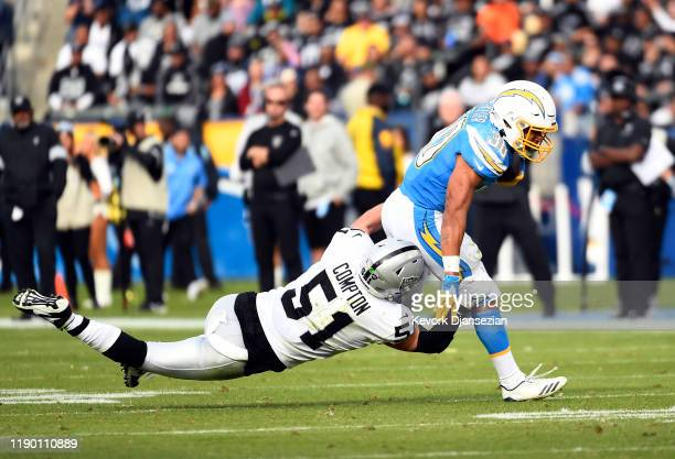 Running back Austin Ekeler of the Los Angeles Chargers breaks a tackle by inside linebacker Will Compton of the Oakland Raiders during the first half...