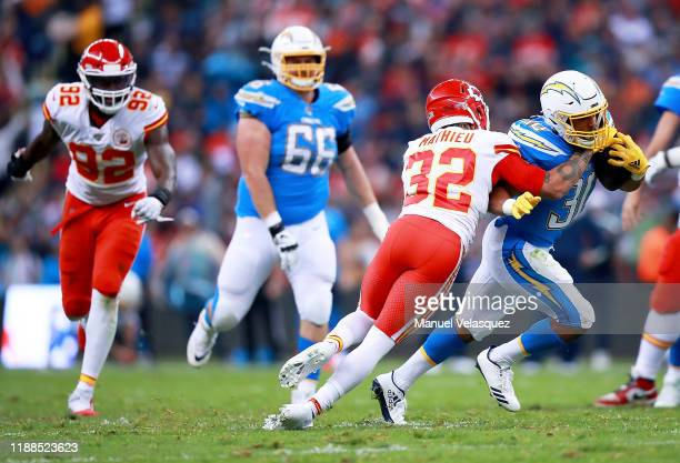 Running back Austin Ekeler of the Los Angeles Chargers carries the ball against the defense of strong safety Tyrann Mathieu of the Kansas City Chiefs...