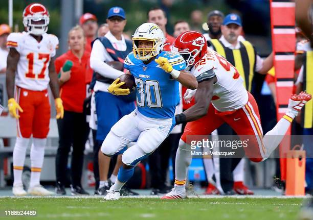 Running back Austin Ekeler of the Los Angeles Chargers carries the ball against defensive end Tanoh Kpassagnon of the Kansas City Chiefs during the...