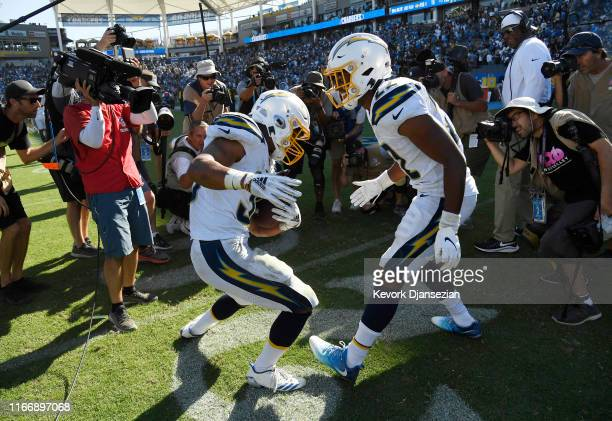 Running back Austin Ekeler of the Los Angeles Chargers dances with Justin Jackson at the end of the game after scoring the winning touchdown in...